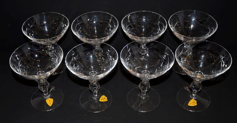Offered is a set of eight signed Tiffin etched crystal champagne coupes or martini cocktail glasses. The etching appears to be botanical in nature. The Tiffin Glass Company operated out of Tiffin Ohio and produced crystal table top under its own