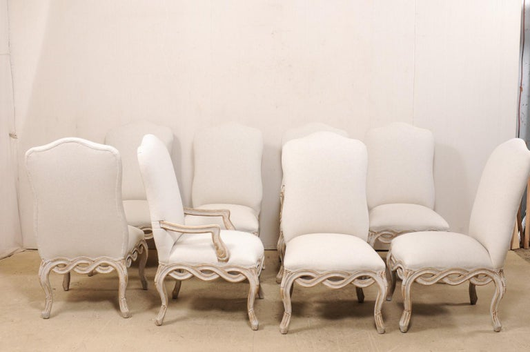 As set of eight American made, Italian Venetian style, carved wood dining chairs with upholstered seats and backs. This vintage set of dining chairs have been beautifully crafted in a Venetian Italian style, and feature subtle hourglass-shaped