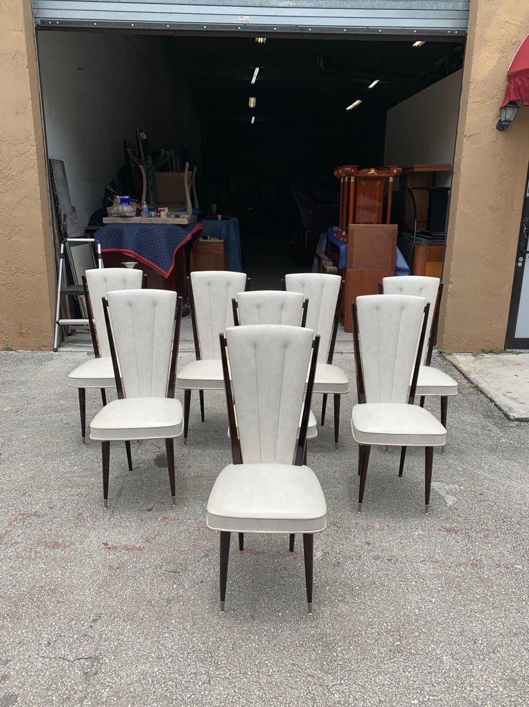 Classic set of six French Art Deco dining chairs solid mahogany, the two front feet are capped with brass. The chair frames are in excellent condition. The Reupholstery is vinyl recommended to be change for all 8 dining chairs but the vinyl look