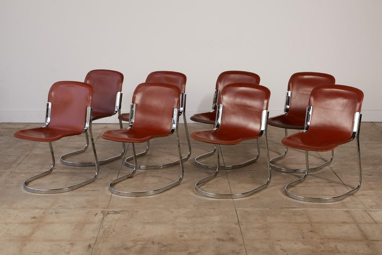 A set of eight dining chairs by Willy Rizzo for Italian manufacturer Cidue, c.1970s. The frame of the chair is formed by two interlocking curves in flat-bar steel with a chrome finish. The seat, a chrome-plated ellipse, has a burgundy-colored