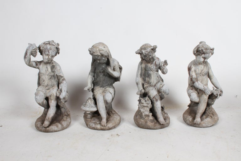 Complete set of antique English garden Four Seasons lead figures, late 19th or early 20th century. Four lead cast children, two girls and two boys, spring: feeding baby birds, summer: with grapes, fall: with wheat and winter: in a robe with a fire
