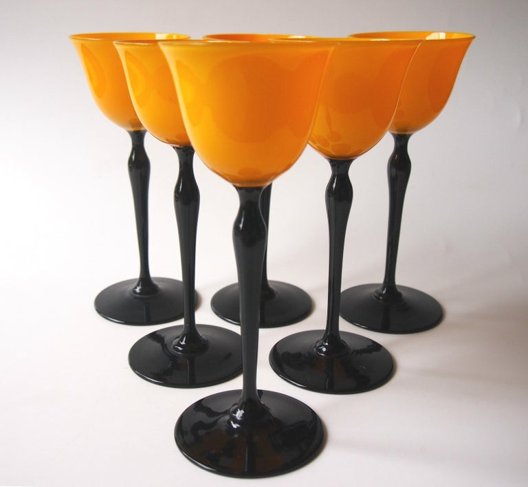 Dramatic set of six 'Tango' Art Deco Harrach wine glasses in vibrant orange on black stems. Bohemian Tango ware was very popular in the USA in the 1920s and 30s and it was made by many companies. It's unusual to be able to identify such pieces to a