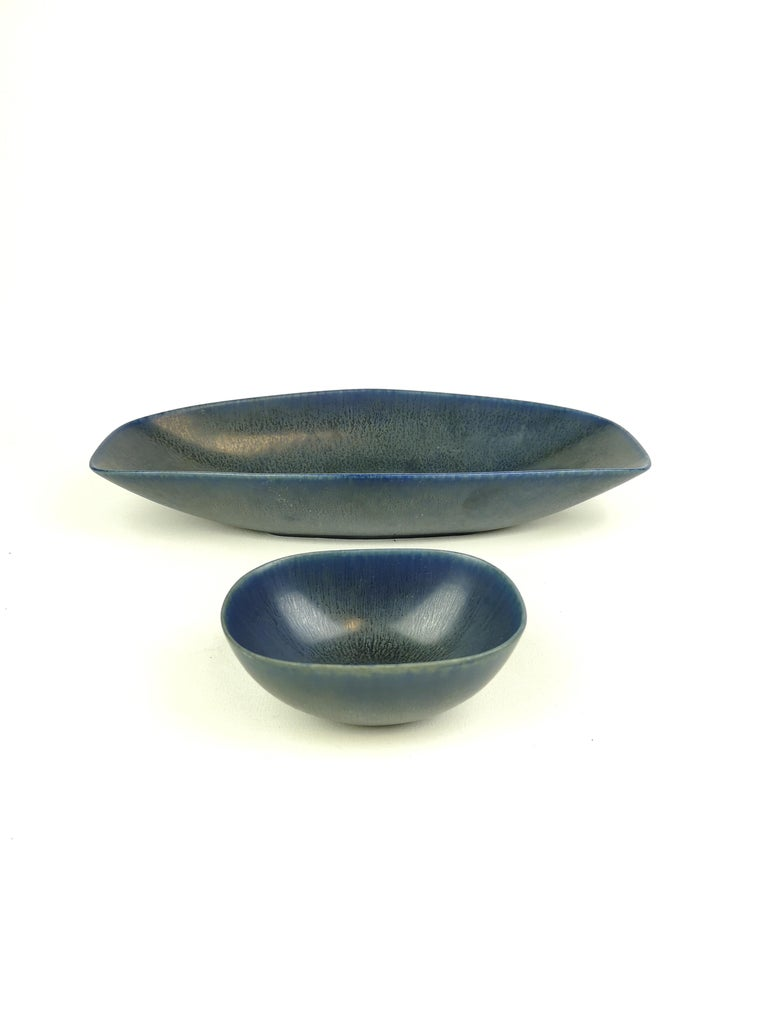 A set of 2 bowls produced in Sweden at Rörstrand and designed by Carl-Harry Stålhane in the 1960s. Beautiful created bowls with a wonderful blue glaze.  Measures: Large bowl 31/14/6 cm, small bowl 12/9/5 cm.   Both are in very good condition.