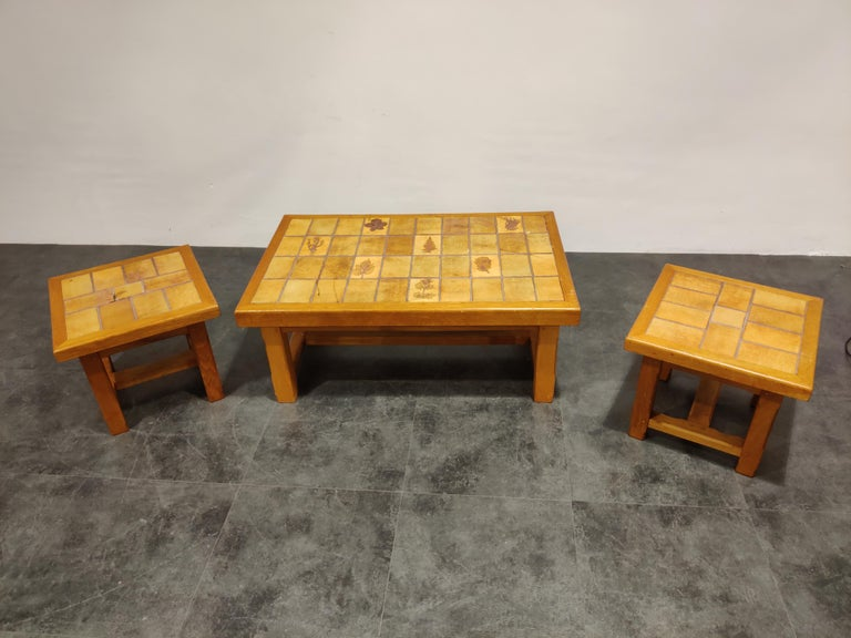 Midcentury coffee table and two side tables with oak frames and earthenware stone table tops in the style of Roger Capron.  Lovely leaf motives   1960s, France  Condition: Some wear, minor little chips but overall acceptable
