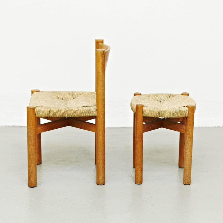 Chair and stool, model meribel, designed by Charlotte Perriand, circa 1950, manufactured in France.  Wood and rattan.  In good original condition, with minor wear consistent with age and use, preserving a beautiful patina.  Charlotte Perriand