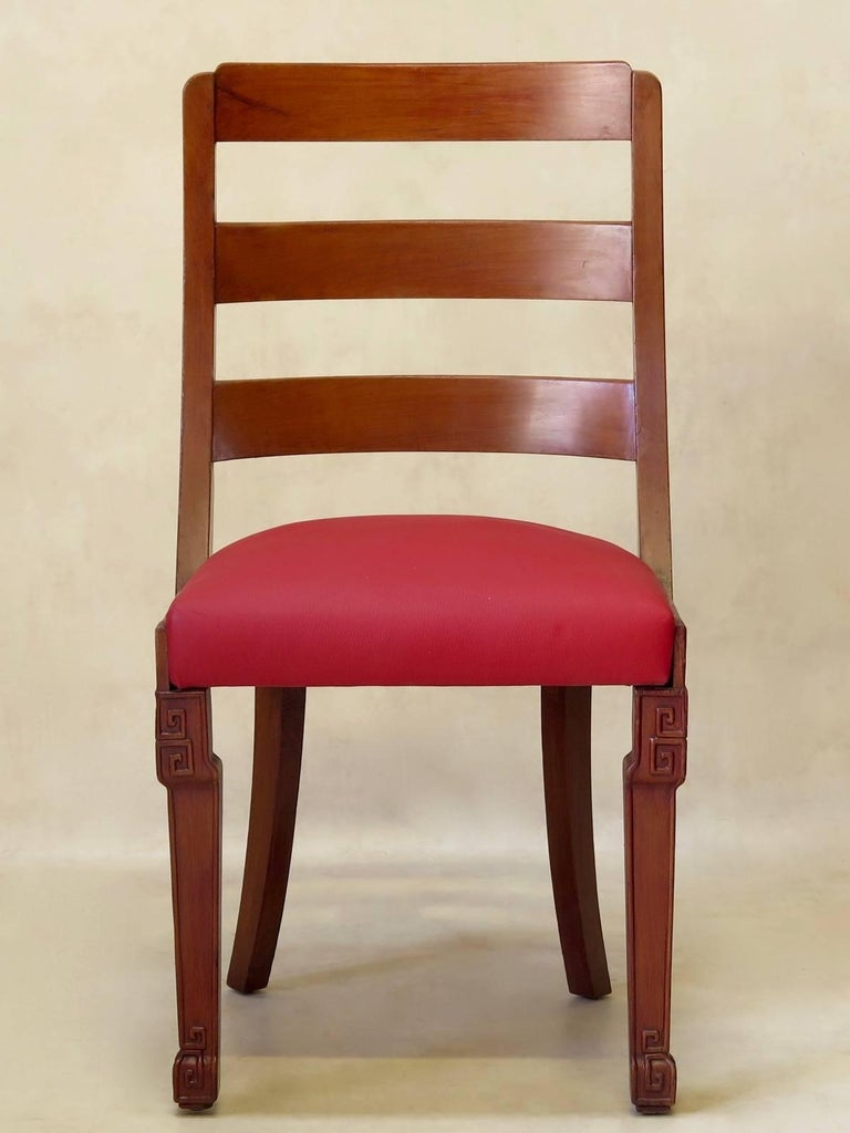 Attractive set of six Chinese Art Deco dining chairs with agreeable, rounded backs, saber back legs, and minimally engraved front legs. The seats are upholstered in cerise red leather.
