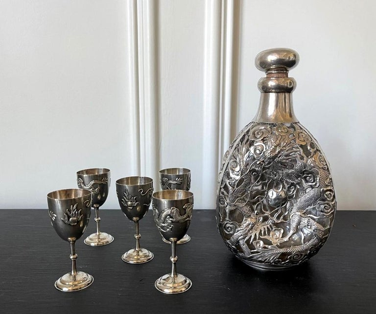 A set of Chinese Export silver drinking set consists of a pinch bottle and five cordials circa 1910s-1920s. Featuring matching elaborate chased relief dragon and cloud motif on surface, this is an rare set of this form by the