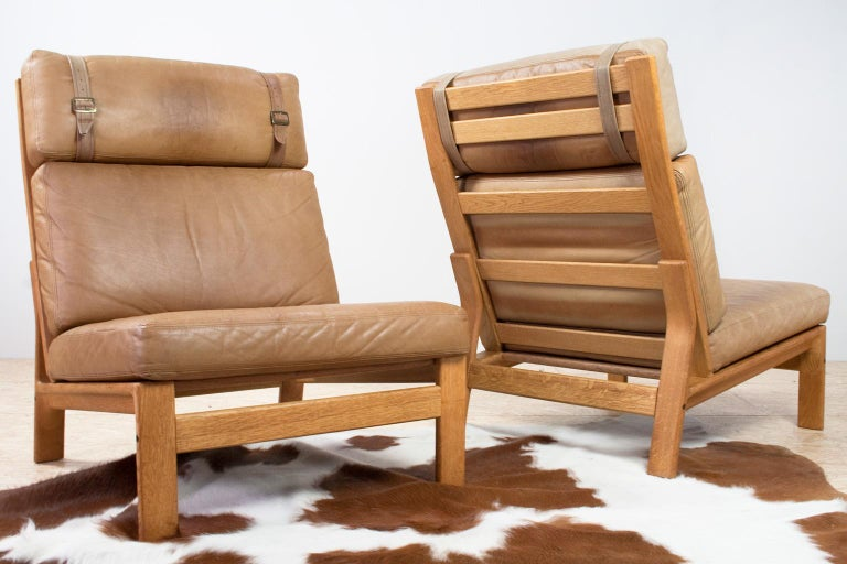 Comfortable and modern set of Danish High back lounge chairs by Danish manufacturer Komfort, 1960s. The chairs are executed in a tan colored soft leather. The upholstery is set on a solid oak wooden frame with slat back. Label manufacturer present.