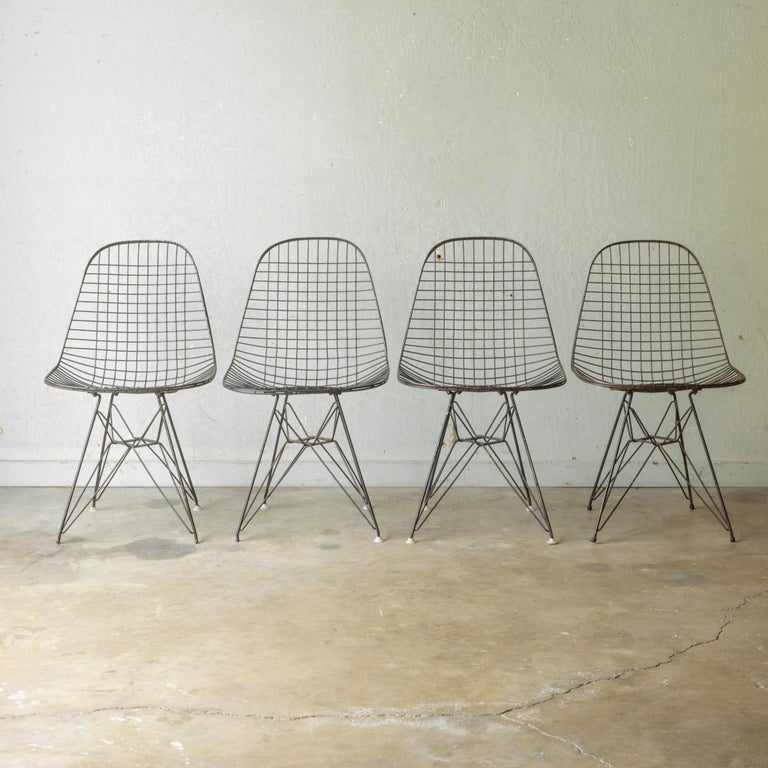 About  An early set of four Eames DKR black wire chairs. Sold as a set only.   Creator: Ray & Charles Eames for Herman Miller.  Date of manufacture: circa 1950s.  Materials and techniques: Metal.  Condition: Good. Wear consistent with age and