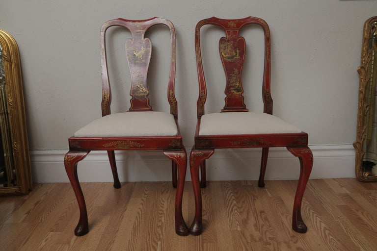 Set of eight red chinoiserie QueenAnne style dining chairs consisting of two armchairs & six sides. Newly upholstered seat cushions. Each back splay is hand painted in a different scene.
