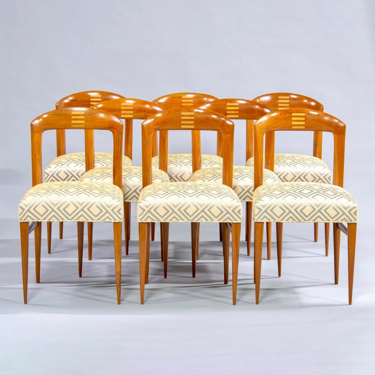 Set of eight polished Art Deco beech chairs, circa 1940. Open backs with curved tops feature inlaid design of stacked bars in contrasting blond wood. Slender, tapered legs. Professionally upholstered with new seats and designer fabric in pale gold