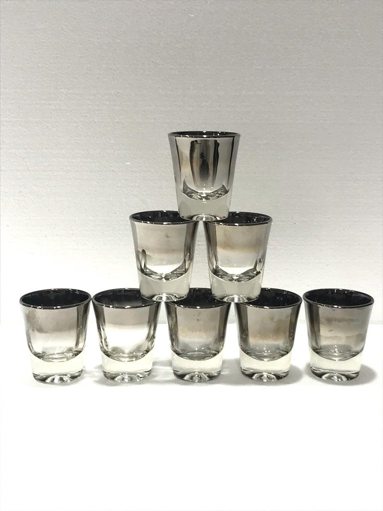 Iconic Mid-Century Modern barware shot glasses set with silver fade overlay design. Gorgeous shot glasses with tapered forms and gradient hues of gunmetal silver along the rims. Makes a chic addition to any barware set.