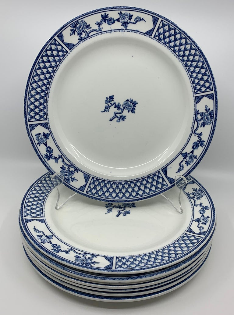Set of eight of blue and white Exeter plates. Eight white English plates with blue lattice border in between floral reserves centering on one cherry blossom sprig. Classic and handsome blue and white plates. Markings
