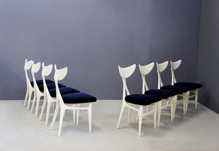 Sculptural set of eight Italian chairs designed by architects Ennio Canino and Viviana Rizzi for Arredamenti Roma, 1954. The set is made of mahogany white paint. Its seat is again lined in blue velvet. The chairs have an anthropomorphic shape almost
