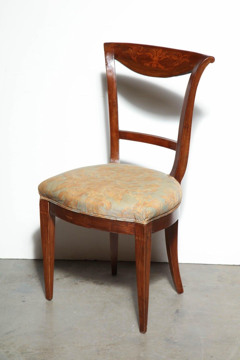 A Fine set of eight French Charles X inlaid dining chairs, with open scrolling backrests, padded cushions seats and square tapered legs.