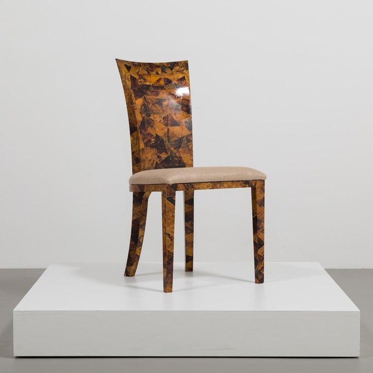 An elegant set of eight coconut shell veneered dining chairs. With sweeping elegant backs and sabre back legs these chairs have a fabulous profile. The veneer is various shades of coconut shell polished and the seats have been upholstered by