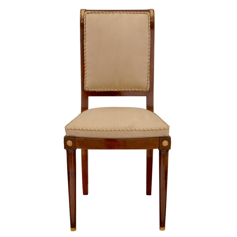A most elegant and complete set of eight Continental 19th century Biedermeier st. mahogany, burl walnut and ormolu dining chairs. Each chair is raised by fine circular tapered front legs with ormolu sabots and lightly curved square tapered back