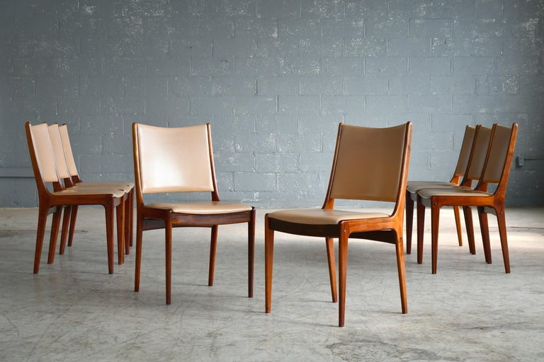 Beautiful set of 8 dining chairs in solid rosewood with leather covered seat and backrest designed by Johs Andersen for Uldum in the late 1960s. Classic light elegant Danish design. Overall very good to near excellent condition with the wood showing