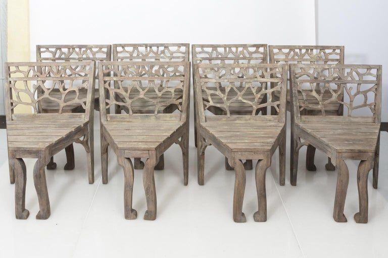 Set of four teak wood garden dining chairs with tree branch tracery on the seat back, circa 20th century.