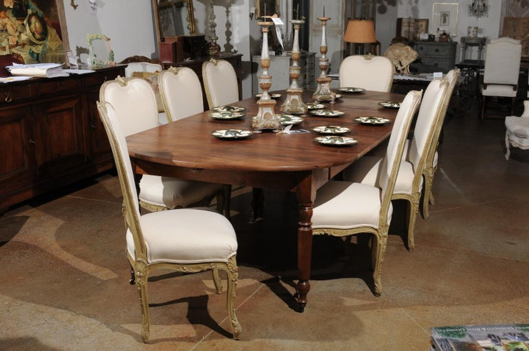 A set of eight early 20th century painted and carved wooden dining room chairs from Marseille Provence, with new upholstery. Created in Southern France during the early years of the 20th century, each of this set of eight dining side chairs features