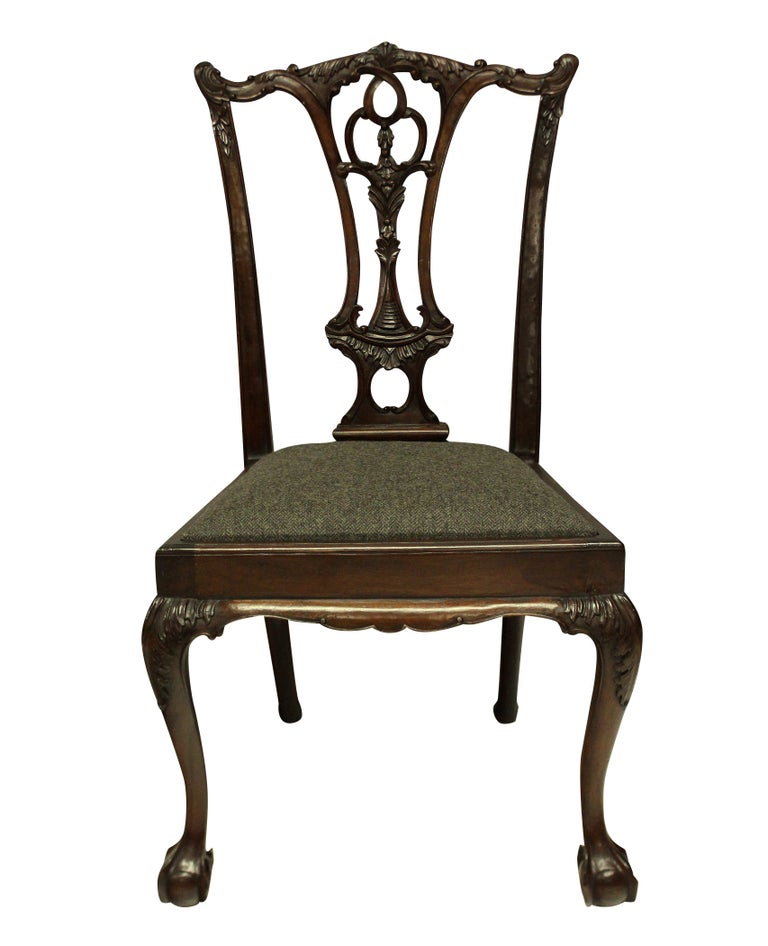 A set of eight English, carved mahogany Chippendale style dining chairs, comprising six chairs and two carvers. Beautifully carved and with herringbone tweed seats.