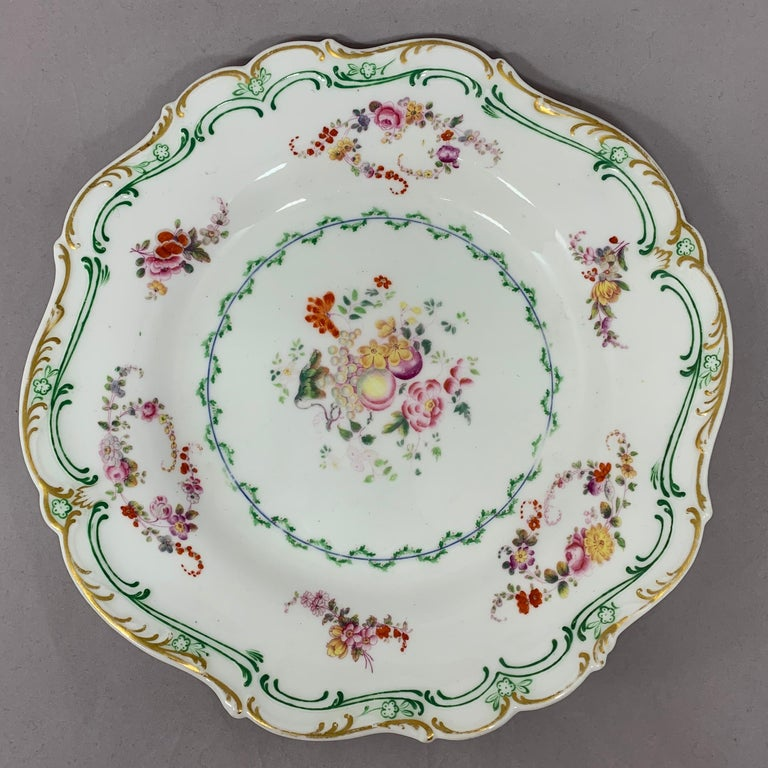 Set of eight English plates. Hand painted plates with floral swags and fruits with gilt rim. England, circa 1840s Dimensions: 9