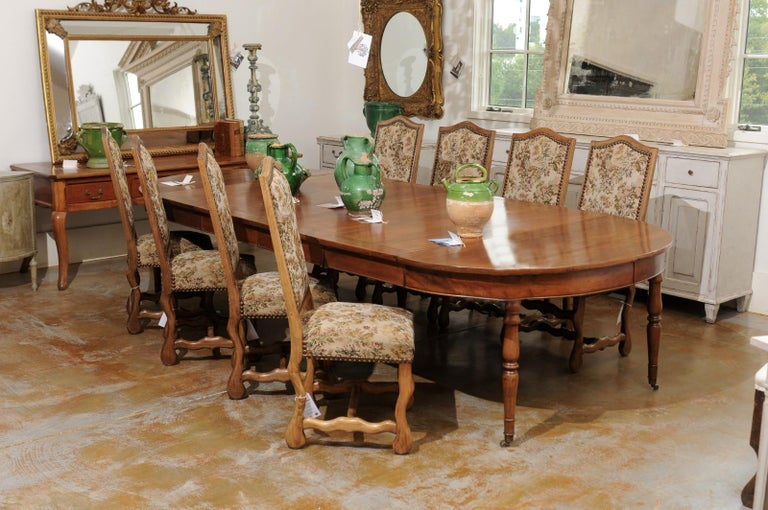A set of eight French Louis XIII style os de mouton dining room side chairs from the 19th century with tapestry upholstery and nailhead trim. Born in France during the 19th century, this set of dining room chairs presents the stylistic