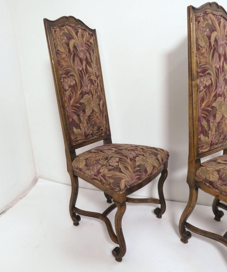 Set of eight high back dining chairs with carved walnut frames in the style of Louis XIV. Re-upholstered recently in a tapestry damask. Made in France, circa 1960s.