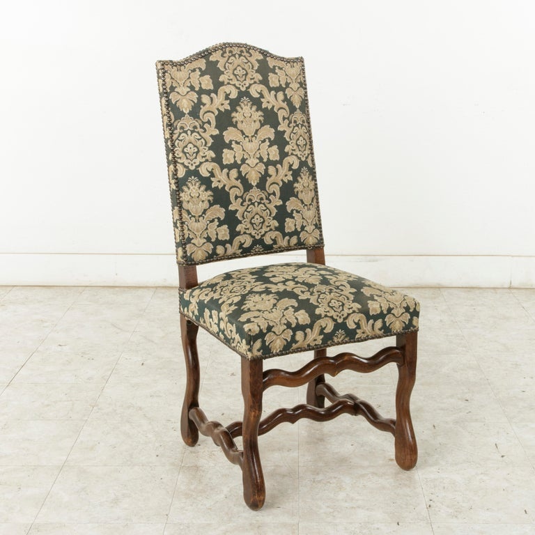 This set of eight French ash mutton leg side chairs or dining chairs from the mid-20th century are of hand pegged construction. These tall dining chairs with arched backs are upholstered in a green tapestry and finished with nailhead trim. The