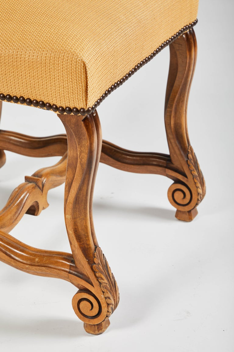 This group of eight side chairs are in the Louis XIV style with H-shaped mutton bone stretchers (Os De Mouton). The wood is a nice warm French oak with nailhead trim. Very strong pegged frame, beautiful patina on wood.   Perfect around your