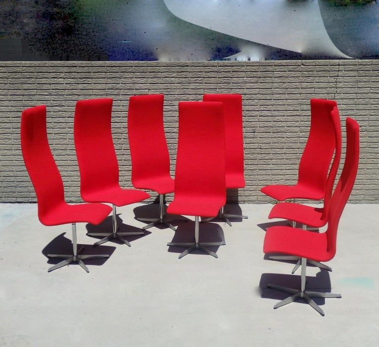 Eight Arne Jacobsen for Fritz Hansen tall back Oxford chairs. Recently covered in Maharam Kvadrat red wool textile.