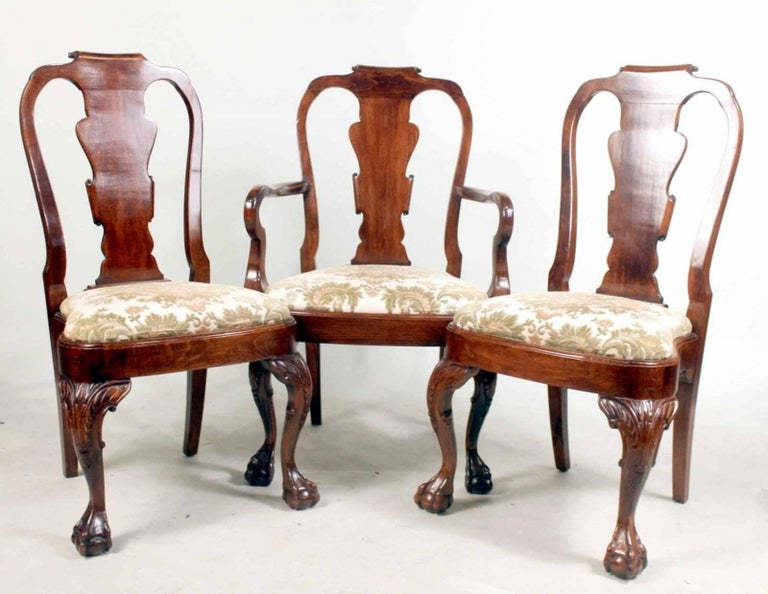A handsome set of eight George I style carved mahogany dining chairs consisting of two-arm and six side chairs, with ball and claw feet.
