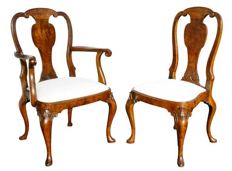 Each with an arched back and vasiform splat with drop in upholstered seat raised on cabriole legs carved with scrolled and bellflower carved knees. Comprising a pair of armchairs and six side chairs.