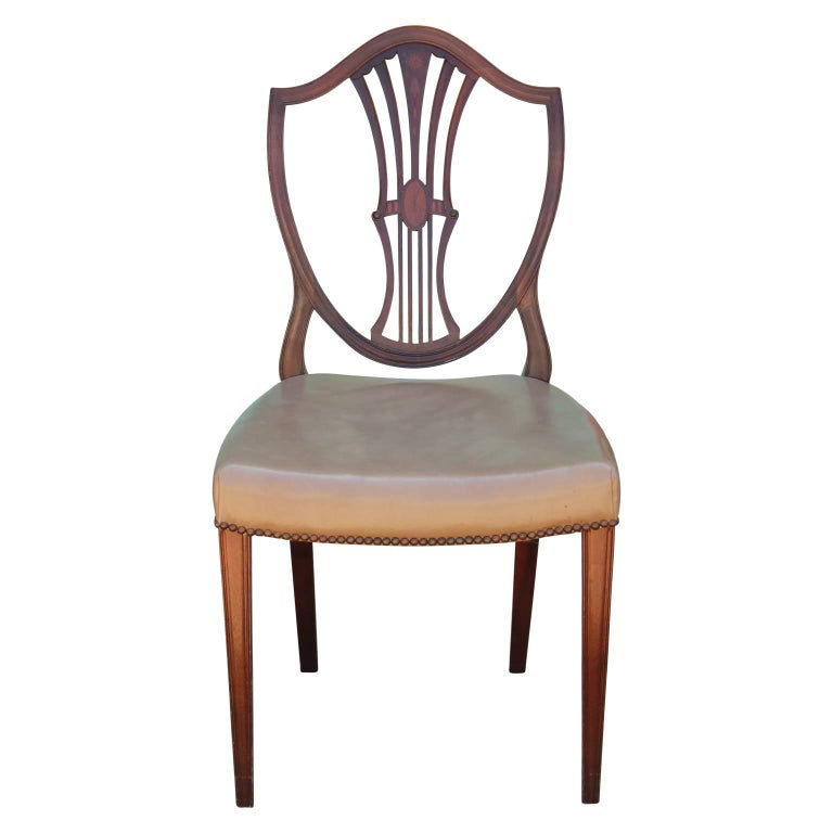 Set of eight George III Hepplewhite dining chairs made from Mahogany with brown leather seats. The backs have a nice inlay. The set features two chairs with arms. In great vintage condition with no real flaws to note. A nice and refined addition to