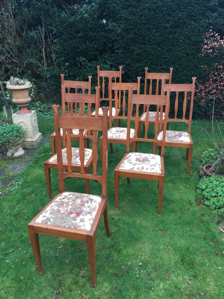 From the furnishers of the Royal Yacht, Cunard liners and top London hotels an extremely elegant set of eight high back dining chairs from the Arts & Crafts period. Made of golden oak the uprights terminating in a heart motif, the backs with three