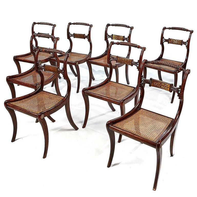 Each dining chair in this set of eight features a simulated rosewood turned and carved rope-twist crest rail ending in brass rosettes, above a brass-inlaid back rail. With a cushion atop a cane seat and sabre legs.