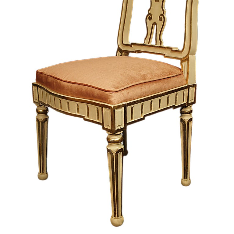 A very high-quality complete set of eight 19th century Italian dining chairs. The patinated cream and gilt chairs are raised on fluted tapered legs ending in a ball design. The molded frieze has reeded gilt sides and square corners. The back of each