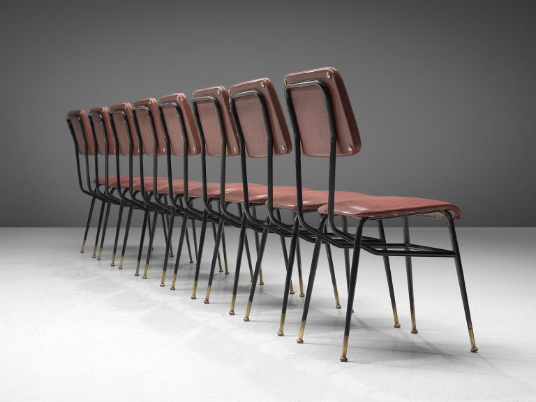 Studio architects BBPR (attributed), set of eight chairs, pink to red faux leather, metal, brass, Italy, 1950s  This set of eight chairs with varnished metal rod structure have strong features of Studio BBPR's designs, and therefore is attributed to