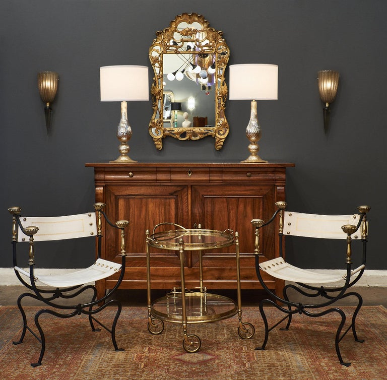 A rare and important set of eight Italian Renaissance style armchairs of hand-hammered iron featuring gilt embossed leather seats. We loved the floral details on the finials, the brass nailheads, and the overall decorative impact of the strong and