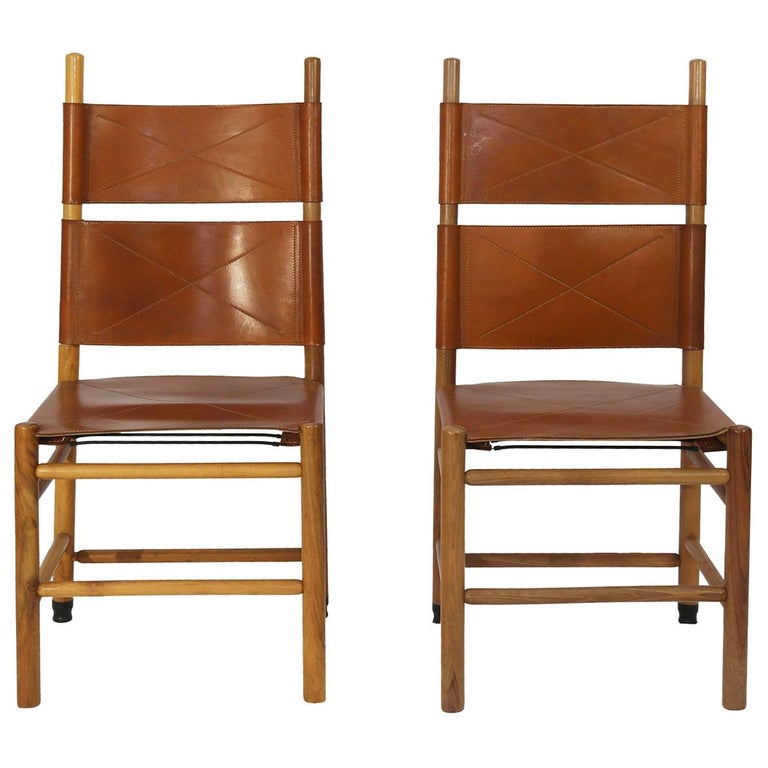 "Set of eight ""Kentucky"" chairs designed by the Master of Design; Carlo Scarpa for Bernini in 1977. Made from oak and walnut timber the chairs retain the original luggage color leather seat and backrest with saddle stitching. Scarpa was inspired by"