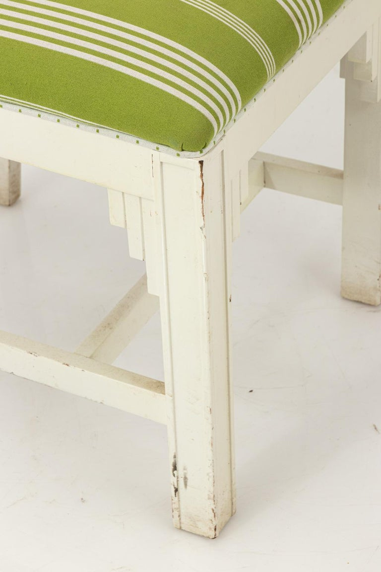 Set of eight white lacquered chairs with upholstered seats and leaf back splat. Please note of wear consistent with age.