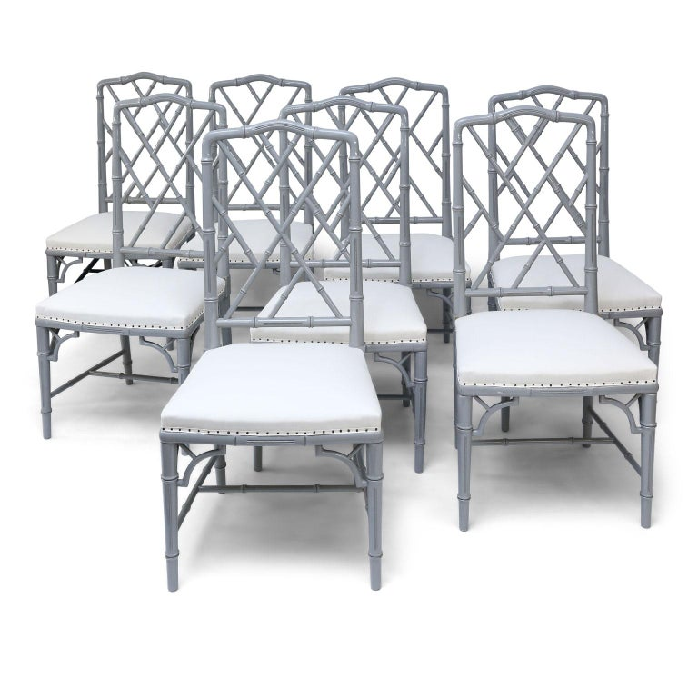 Set of eight-light gray lacquered dining chairs from France dating to the 1970s. Faux bamboo frames carved in Chippendale style and finished in a warm gray lacquer. Upholstered in white ticking (meant to be covered in your own fabric). Finish is