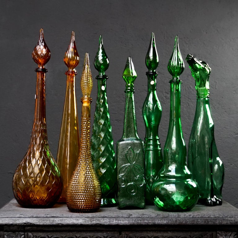 Very colorful and decorative set of eight largeItalian glass 'genie bottle' decanters with different green and amber glass motifs and colors.  All bottles have their stopper and are different in color, design, shape and size (height with