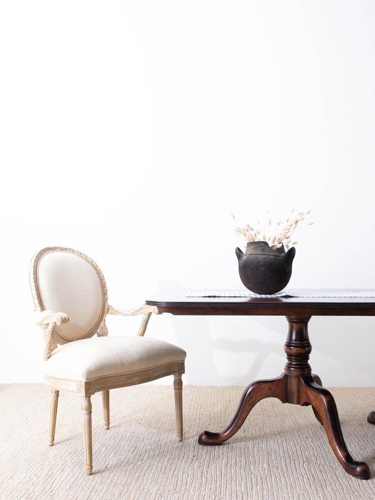 Bespoke set of eight dining armchairs made in the Louis XVI Gustavian taste by Century Furniture featuring blonde hardwood frames. Hand carved with decorative laurel swag on the arm supports and a floral crest on the round backs. The generous frames