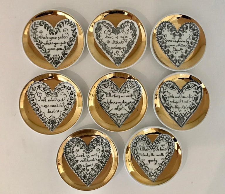 A full set of 8 LOVE series coasters by Piero Fornasetti. Each coaster has a gold border surrounding a heart with its own unique motif surrounding a different saying or proverb. This series was not produced in large numbers and full sets are more