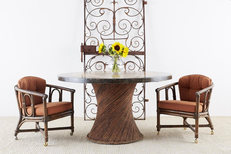 California organic modern style matching set of eight genuine McGuire lounge chairs or game table chairs. Constructed from bamboo rattan poles with a barrel-back or horseshoe form frame. The backs are decorated with oval supports and the seats have