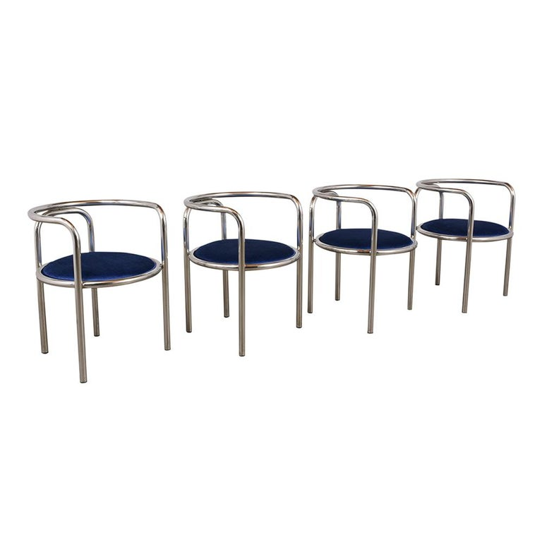 This set of Eight Stylish Mid-Century Modern Chrome Dining Chairs have been fully restored, and feature a barrel back chrome frame in a very good condition. The seats have been newly upholstered with blue velvet fabric. The chairs are comfortable,