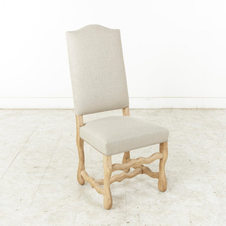 Newly upholstered in France in a beautiful neutral colored linen, this set of eight mutton leg dining chairs features sturdy hand pegged construction, providing stability to the frame. The unfinished oak and natural linen lend a light, airy feel to