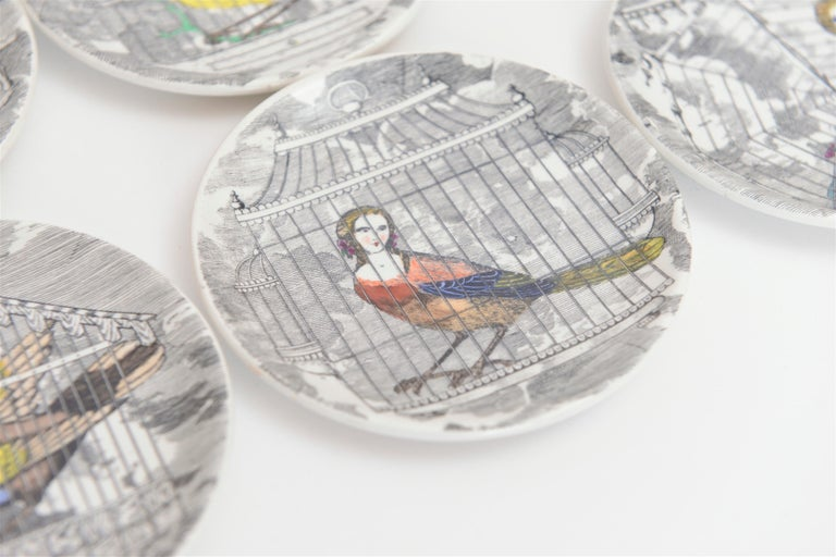 A complete set of eight Piero Fornasetti ceramic drinks coasters, entitled 'Le Arpie Gentili'. These 1950s coasters each depict a mythical half bird, half human figure held within a cage. This beautiful Fornasetti design is very rare and highly