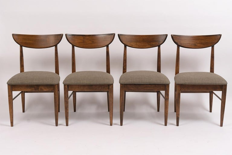 This set of eight Mid-Century Modern dining chairs have been restored and feature a new walnut color with a semigloss lacquered finish. The chair has solid handcrafted maple wood frames with a curved back design for added comfort. The set has been